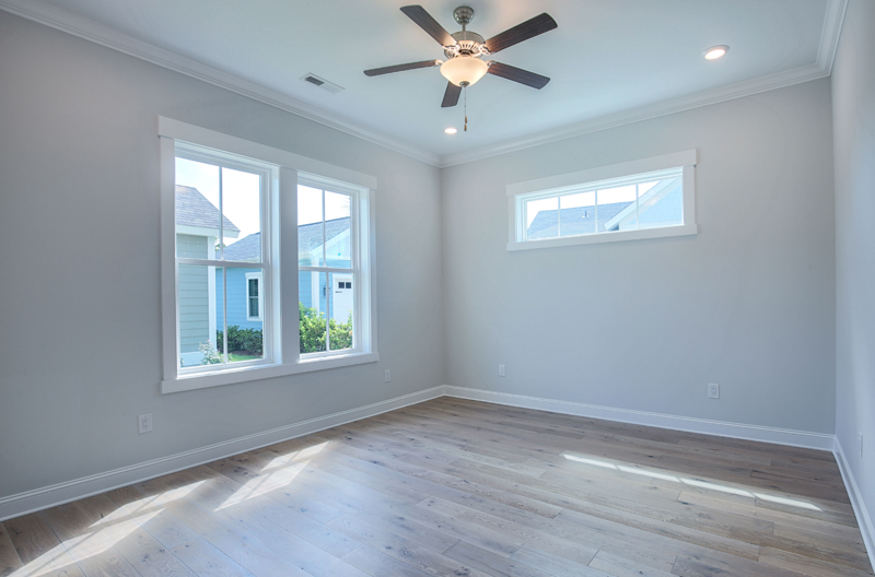 Big windows in vacant room with fan
