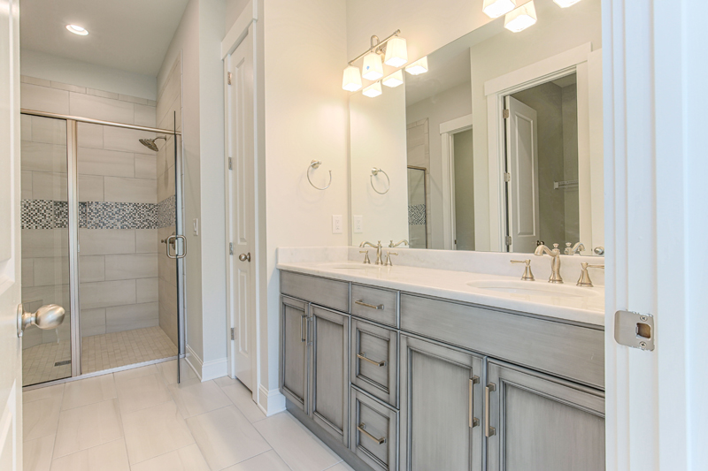 Grey Cabinets and dual sink vanity with walkin shower