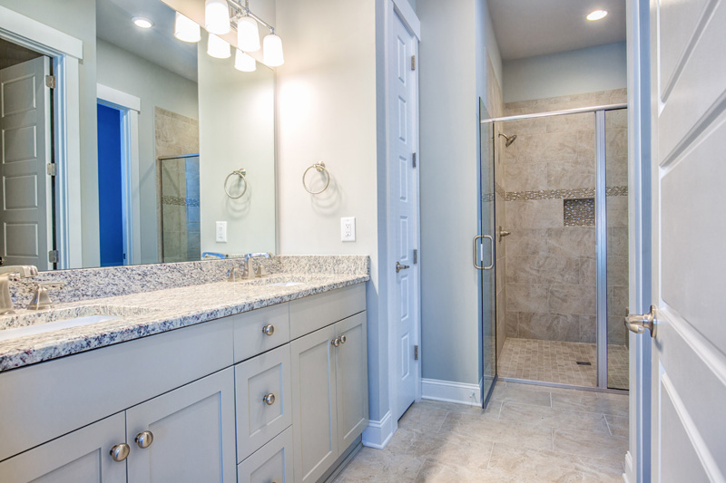 White cabinets and light counters on dual sink vanity near walk in shower