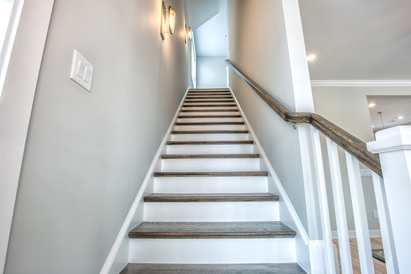 Looking up a staircase with white and wood