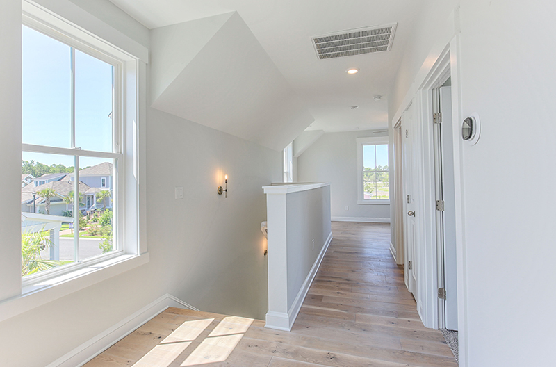 Looking down a hall with wood flooring near bright windows