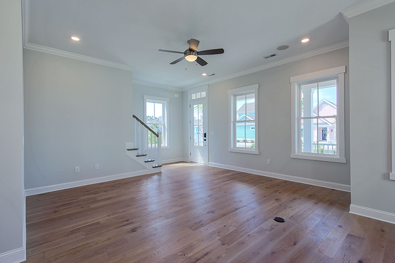 Open living room with wood floors and windows